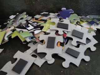 I like this idea! Put magnets on the backs of puzzle pieces. Do puzzles on metal cookie sheets in the car! Or on fridge! Genius!