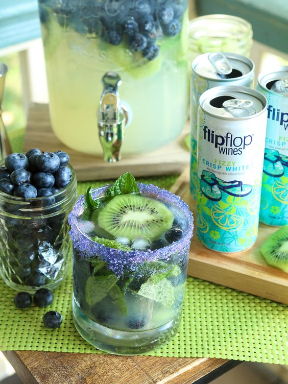 Wrap up the summer with major flippin' flavor! Make our flipflop Kiwi Blueberry Sparkling Mojito! Blend 6 peeled kiwis, ¼ cup fresh lime juice, ~ ½ cup sugar, and 4 oz of mint leaves in a food processor. Gently crush the first 6 oz blueberries using a muddler. Moisten the rims of your glasses with a lime and garnish with colored sugar. Add a few blueberries, pour in the kiwi puree, gently stir in the rum and our Fizzy Crisp White. Add ice. Garnish as needed with mint leaves and kiwi slices.