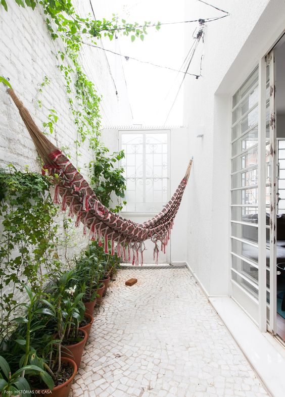 Área externa de casa tem rede de balanço, piso de pedras portuguesas e vasos de barro.