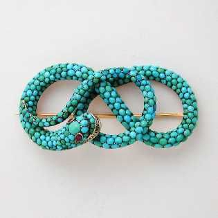 A Georgian entwined turquoise snake brooch, the entwined body pave-set with cabochon-cut turquoises, the eyes set with oval shaped faceted rubies, set in silver, estimated to measure 2.7 x 5.5 cm, gross weight 22.2 grams, circa 1840:
