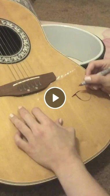 Moça é uma Artista desenhando em seu violão.