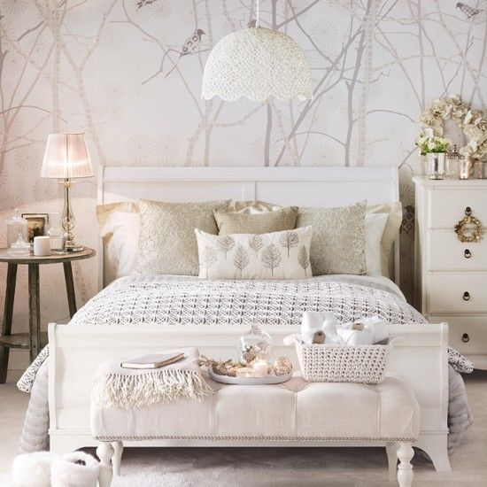 This sophisticated white bedroom is decorated with a stylish bird pattern wallpaper as the backdrop to luxurious cushions, throws and a cosy rug
