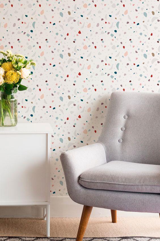 Papel de parede Coleção Terrazzo, uma releitura da estampa granilite, com desenhos nas cores azul, cinza, vermelho, bege e salmão. Fundo branco liso.