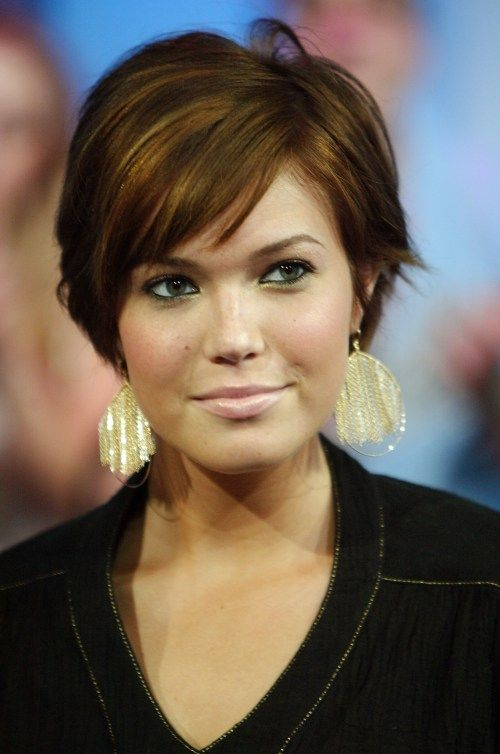 mandy moore short hairstyle with straight slicked back hair, side parted and brightened with warm golden and honey highlights.**She prefers straight side swept bangs and messed up styles, sometimes with wet sexy look.Those looks where she styles her pointy side flicks outward are definitely the sharpest. She also benefits from side tresses, caressing her cheeks and softening her angular jawline.Loose curls in short-to-medium bob haircuts also work fantastic for her face shape, masking its…