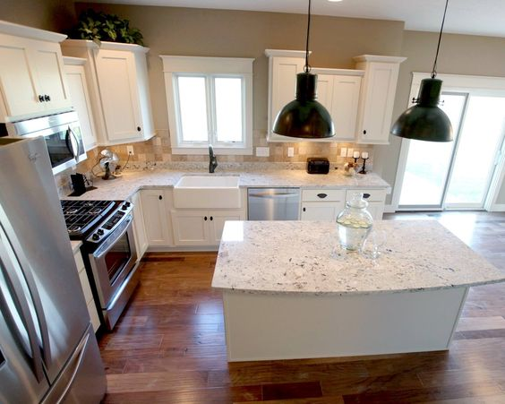 This white setup has mostly cabinets on one side and appliances on the other. It also features an island to provide a little bit more counter space.