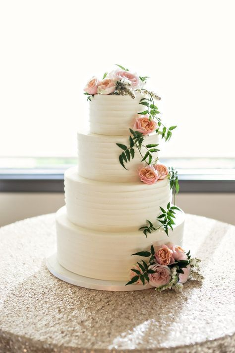 Rustic buttercream-frosted wedding cake decorated with organic pink flowers and greenery, created by The Butter End Cakery.