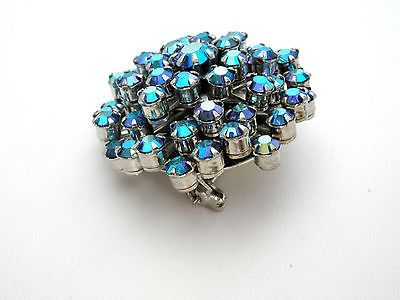 This is a vintage Weiss blue aurora borealis rhinestone brooch. You can use your imagination with brooches. They can be worn in your hair, on belts or sashes, even men are wearing them. This pin is si