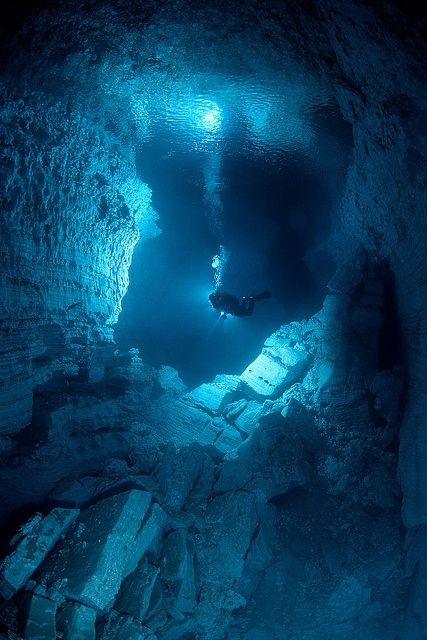 Explorer inside Orda Cave, the biggest underwater gypsum cave in the world, Russia