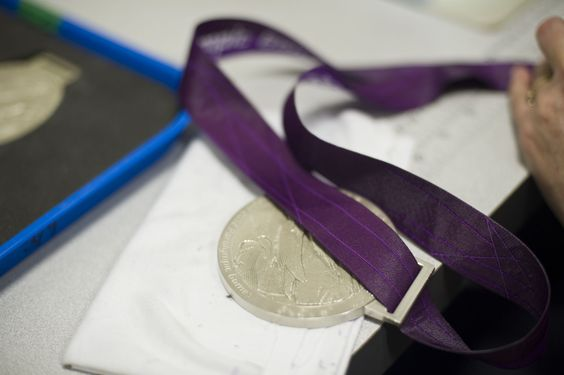 Attaching the ribbon to a London 2012 Paralympic medal at The Royal Mint