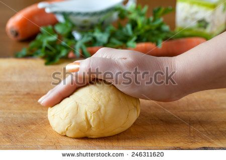 Hand above pasta dough on a cutting board with carrots and parsley in the background.