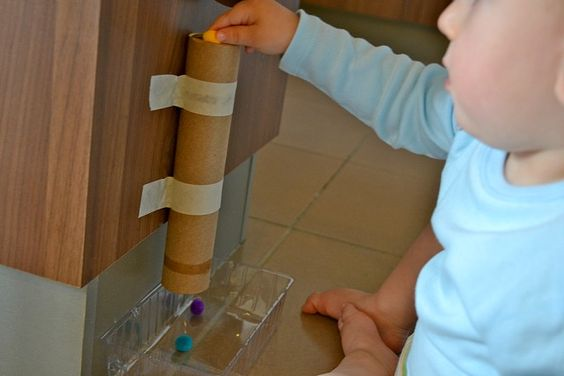 Putting pom pom into cardboard tube, fine motor skills, discovery....excellent activity while Mommy is in the kitchen!
