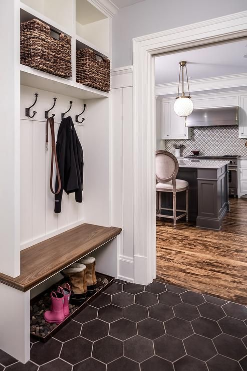 Clad in black hexagon floor tiles accented with white grout, this well appointed mudroom features a river rock boots tray placed beneath a built in wood bench fixed against a white shiplap backsplash fitted with oil rubbed bronze hooks mounted under white overhead shelves stuffed with wicker baskets.