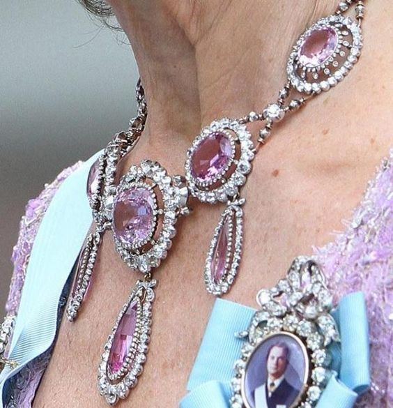Josephine Bonapart's Pink Topaz Demi-Parure consists of a necklace with three pendants, a large corsage brooch and a smaller one. On Queen Sylvia of Sweden.