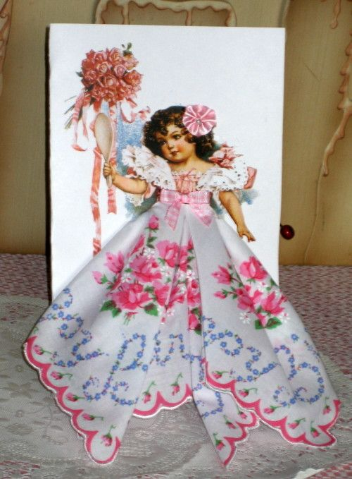 """A darling old-fashioned girl holds a bouquet and is wearing a sweet floral hanky! So cute! 5x8 card comes in a clear sleeve and includes envelope. """"This Little Lady Wears a Keepsake Hanky Just for You"""