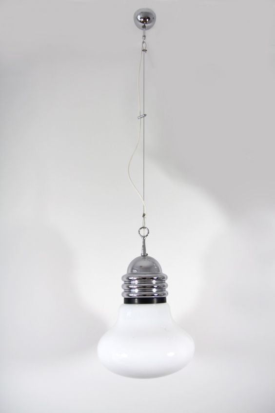 This model Arianna ceiling light was designed by Piero Brombin in the 1960s and manufactured by Artemide in Italy in 1965. It features an upper chrome fitting and a glass shade. The canopy and the suspension are made from chrome as well. The lamp height can be adjusted. This lamp remains in a very good vintage condition.