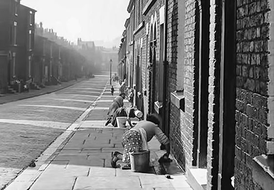 "Liverpool..Proud lasses ""Donkey Stoning"" the front steps of their back-to-back houses..Stones were stamped wi a donkey and supplied by a firm in Wigan..   