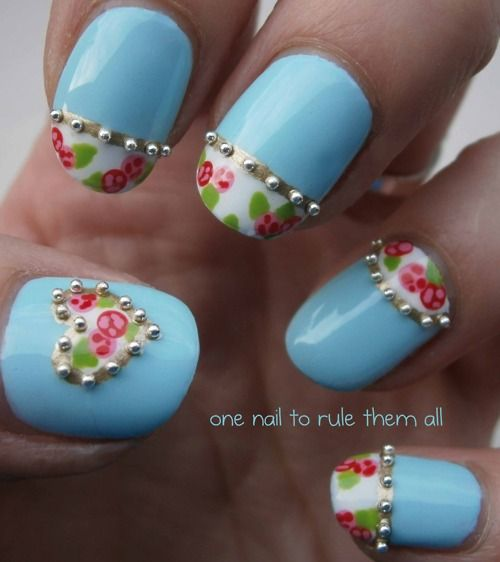 =Paint your nails with a pretty sky blue polish, and then tape off french tips or moons and paint them white. Draw in the little roses with pink and red, and then outline the white areas with gold. Add in little beads and seal off your design with topcoat.