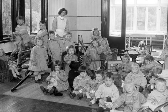 June 1916: Boys and girls playing indoors at the Montessori Children's Villa on a rainy day, watched by a nurse.