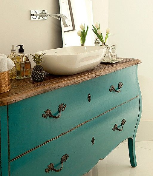 No lugar do gabinete, a cômoda turquesa foi adaptada para o cano e o sifão. Projeto de Luita Trench