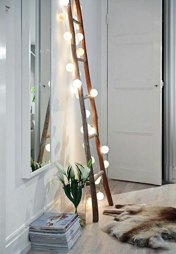 skandinavische Einrichtung im Wohnzimmer Holzleiter mit Lichterkette