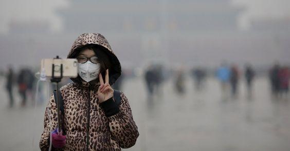 20151209 - Usando máscara antipoluição, mulher tira selfie na praça Tiananmen, em Pequim, logo após cerimônia de hasteamento da bandeira nacional chinesa. A cidade entra no seu segundo dia de alerta vermelho devido ao alto nível de poluição do ar, que está quinze vezes superior ao nível máximo recomendado. Esta é a primeira vez que o alerta chega a esse nível. PICTURE: Damir Sagolj/Reuters