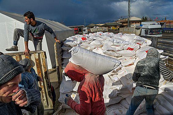 Un gruppo di uomini carica i preziosi sacchi di farina forniti dalla Mezzaluna Rossa turca su un camion diretto in Siria.