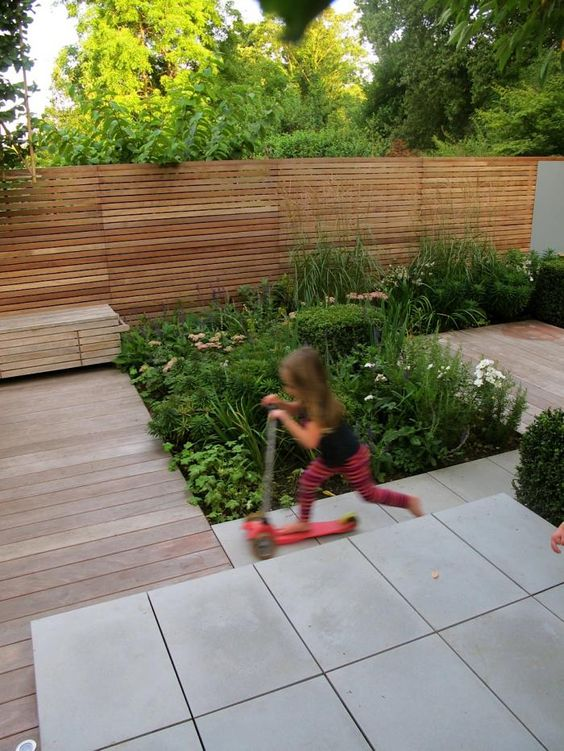 Contemporary Grey Sawn Sandstone Paving is complemented beautifully by the lush planting in this urban garden.