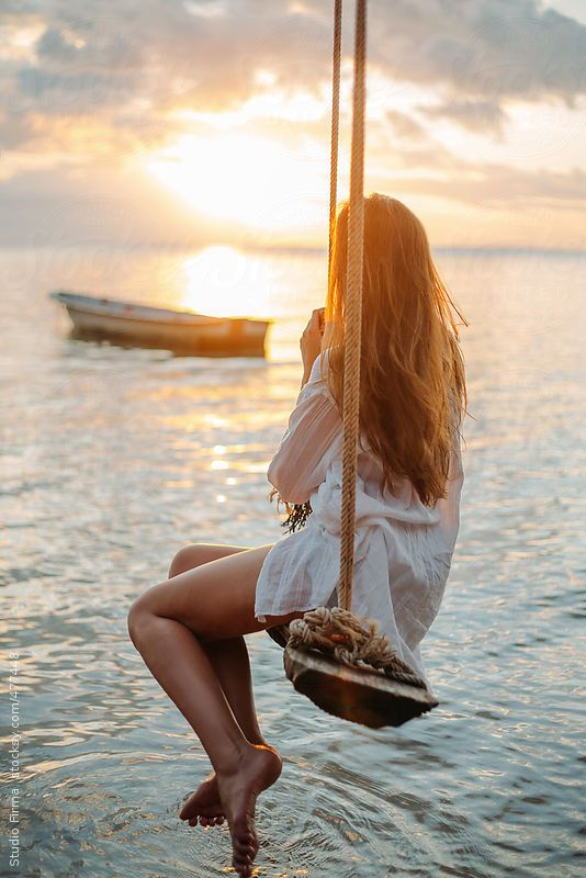 Girl on a swing in sunset