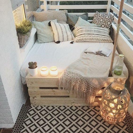 sundurma fikirleri, ahşap kapaktan yapılmış kanepe, beyaz kapaklı ve birçok soluk desenli yastık, birkaç yanan mum, saksı bitkileri ve battaniye