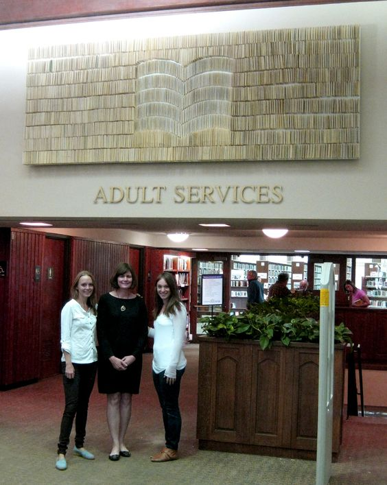 Highland Park (Ill.) Public Library Director Jane Conway (center) with Crystal Grover and Linsey Burritt of INDO design studio in front of the library's new Open Book sculpture.