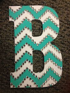 Paint wooden letter base color, Draw pattern with pencil when paint dries, Use painter tape to cover every other line, Paint untaped lines second color, Let dry then carefully peel tape off, Add rhinestones with super glue or decorative tacks.:
