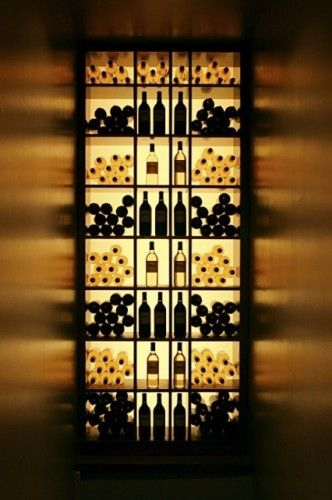 Back-lit shelving allows the shape of the bottles to be used almost like art. The play of light off the walls adds another interesting set of textures and color