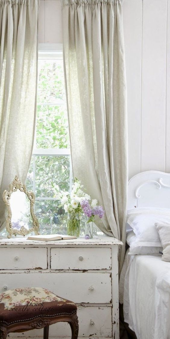 French Country style in feminine romantic bedroom with vintage bedside chest, pretty curtains, and shabby chic decor. Romantic European Farmhouse Bedroom Decor Ideas!