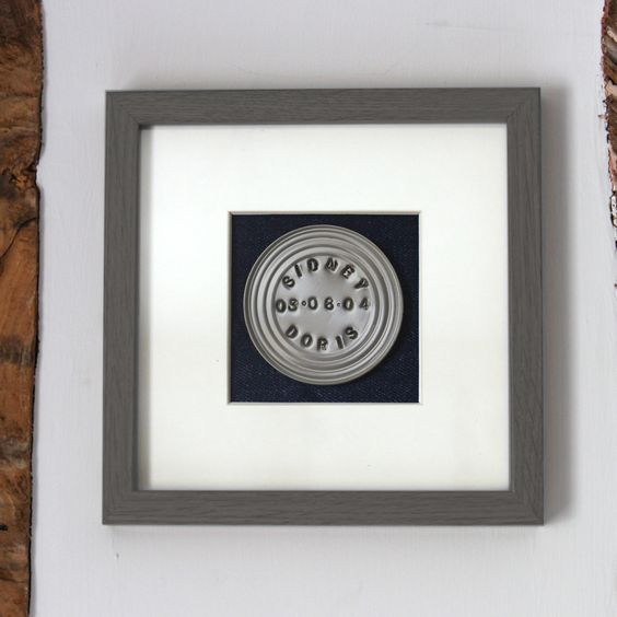 A brilliant gift for a tenth wedding anniversary. Handstamped, up cycled tin mounted on heavy dark blue denim in a grey frame. Personalised, of course!