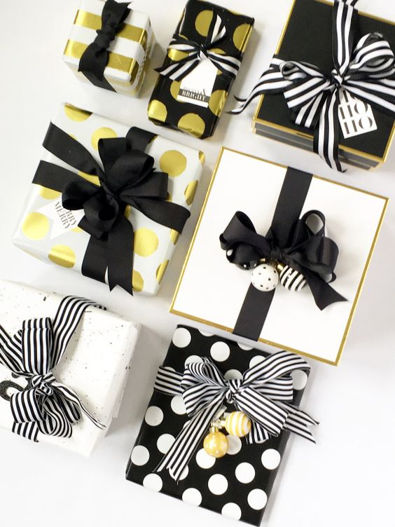 Black, gold and white holiday gift wrapping inspiration by jane-can.com. We love to combine polka dots and stripes when we wrap presents.