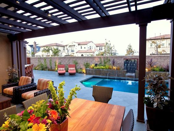 A fully furnished outdoor patio overlooks a unique pool with cascading water fountain. A pergola provides shade for outdoor entertaining while dividing the space from the pool deck.