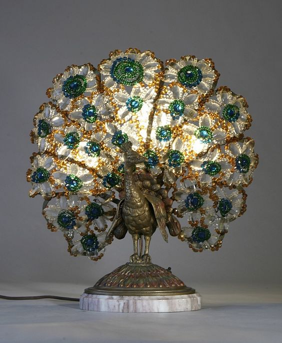 "Peacock Lamp, circa 1900: A period lampshade on a bronze & marble base featuring the body of a stylized peacock. Features ornate glass bead-work on a bronze framework in green, gold & amber tones. The shade of the lamp forms the ""tail"" of the peacock, while the bronze base delicately represents the body of the animal:"