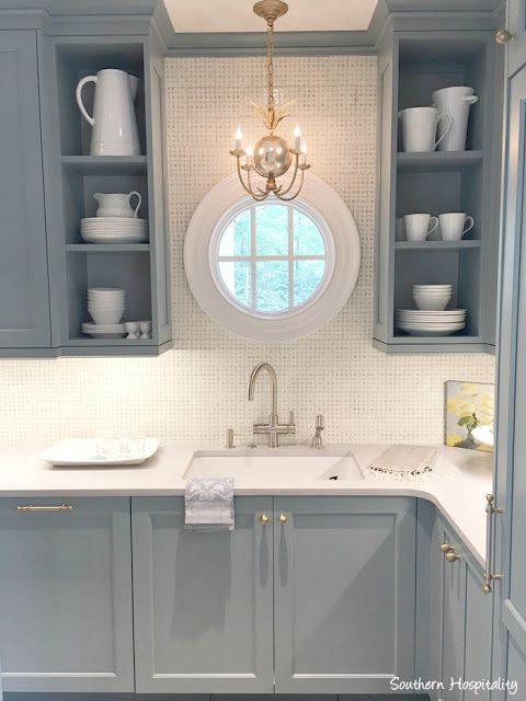Butler pantry with round window and chandelier above sink. Stunning traditional style kitchen with light blue painted cabinets, hammered brass hardware arch window over farm sink, and waterfall marble island. Design Galleria Kitchen & Bath Studios. Lauren Deloach. Southeastern Designer Showhouse & Gardens. #bluekitchen #roundwindow #classickitchen #scullery