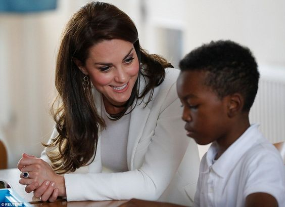 Kate made conversation with a young boy during a lesson in his East London school... Catherine's nautical looking outfit -- white top and jacket, navy cropped trousers with gold button detail, flat shoes with tassels. June 16 2017