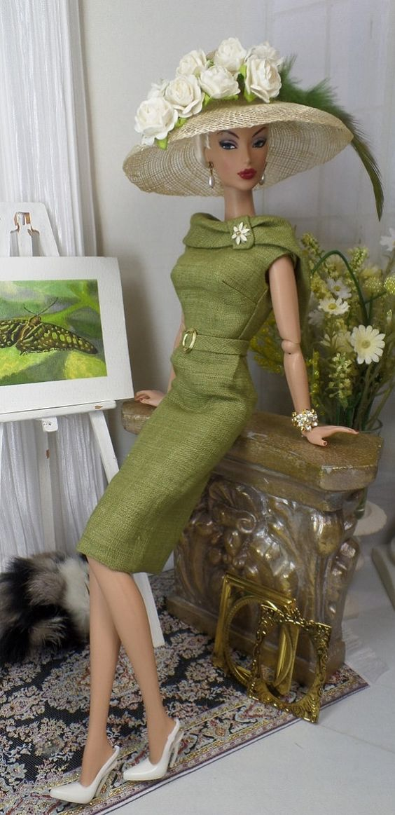A classic sheath cut from olive handkerchief linen, fully lined in china silk, and features a portrait collar bodice with tab, two tone daisy brooch, attached belt with gold-tone buckle and button over snap back closure. Natural Sinamay hat decorated to match Doll, shoes, jewels, purse, sunglasses, and diorama accessories not included.