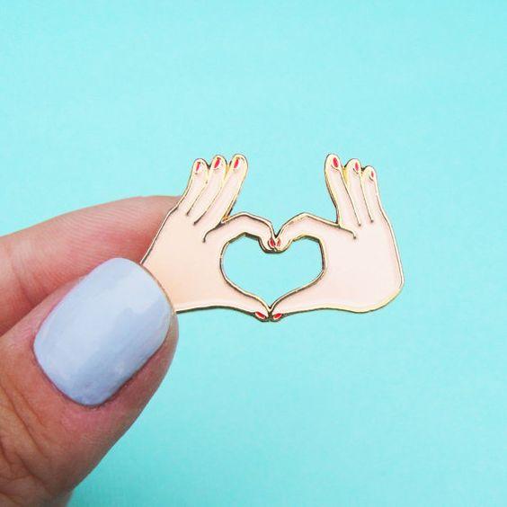 Pins petites mains en coeur Amour.  Réalisés en édition limitée en métal finition or brillant, et émaux colorés rose pâle et rouge. Ce pins a 2 attaches de type papillon.  Ce pins mesure 3 x 2 cm.: