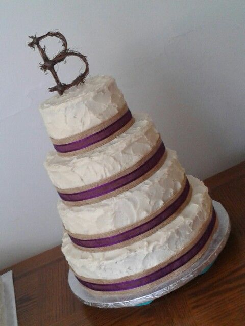 Four Tier Country Wedding Theme Cake Covered In Textured Buttercream With Burlap And Purple Ribbon Accents