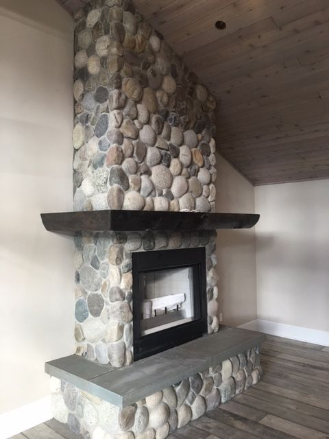 A fabulous update to a fireplace at the lake - natural river rock thin stone with bluestone hearth www.nimasonry.com