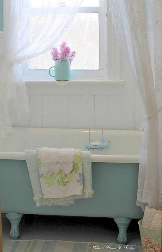 Blue and white clawfoot tub in a bathroom with a window above it.