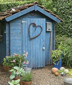 Beautiful blue painted shed with wooden heart on the door and tiled roof
