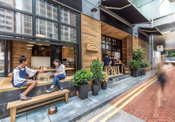 壁際に縁側的なベンチシートのある開放的なカフェのダイニングと右サイドのカウンター席