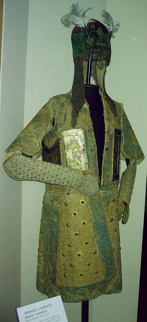Chilta hazar masha (Coat of a thousand nails), kulah khud (helmet), bazu band (arm guards). Indian armored clothing made from layers of fabric faced with velvet and studded with numerous small brass nails, which were often gilded. The padded coat, minus its nails, is known for short as a chilta. Fabric armor was very popular in India because metal became very hot under the Indian sun. This example has additional armor plates in the chest area. Royal Armouries in Leeds, England.