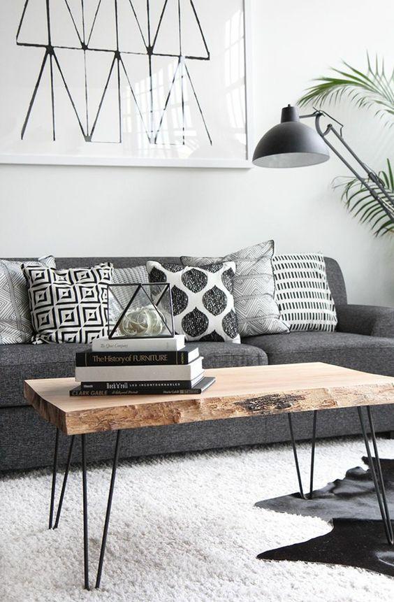Wunderhübscher Hingucker-Couchtisch mit dicker Holzplatte im Naturlook, weicher weißer Teppich und eine graue Couch mit gemusterten Kissen. ♥: