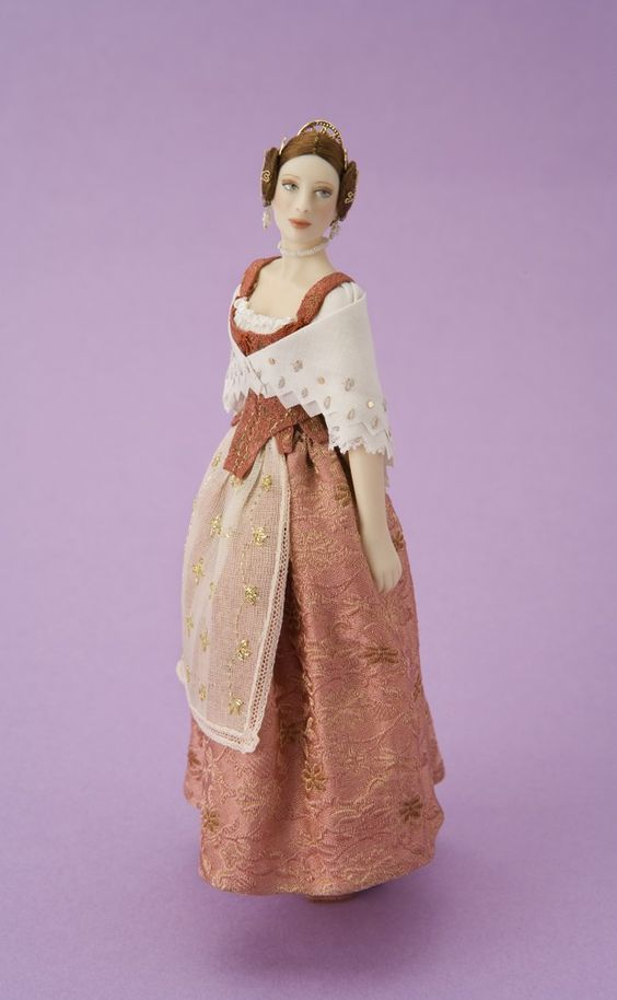 """NAME: Mireia  COUNTRY: Spain  AREA: Valencia  PRICE: 800 euros  Traditional dress from Valencia, inspired by a real costume (18th century) in the """"Museo del Traje"""" in Madrid, Spain. The corset, shoes and skirt are made of silk brocade. The apron is embroidered with gold thread and the shawl trimmed with sequins."""