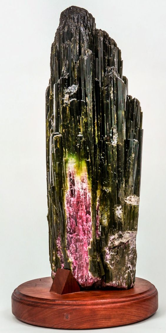 Watermelon Tourmaline Crystal. One of the world class specimens found in the Cranberry pocket of the Cruziero Mine in Minas Gerais, Brazil. It's also one of the two largest and well preserved long single Crystal Watermelon Tourmalines discovered to date from Cruziero. The many long pinnacles in the crown demands attention and the bright pink/red colors are a promise of what lies within. This and more rare mineral specimens for sale on CuratorsEye.com